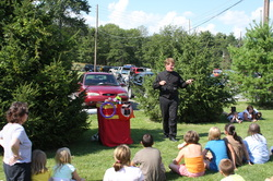 Mark Clark performing his magic show for a group of children at a picnic.